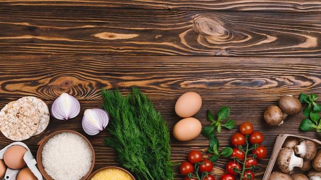 Verdure fresche; uova e chicchi di riso e torta di riso soffiato sulla scrivania in legno Foto Gratuite