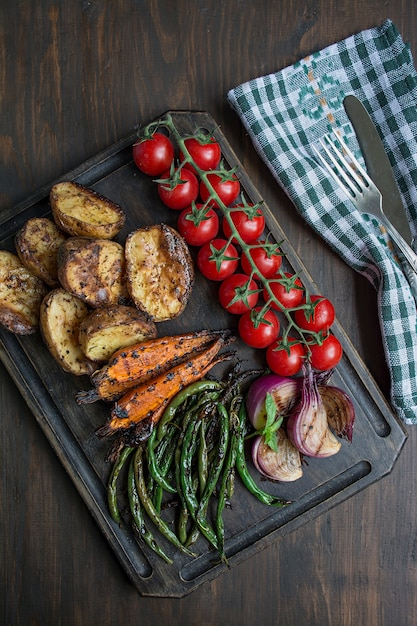 Verdure grigliate su un tagliere su un tavolo di legno scuro. tavolo in legno scuro. Foto Premium