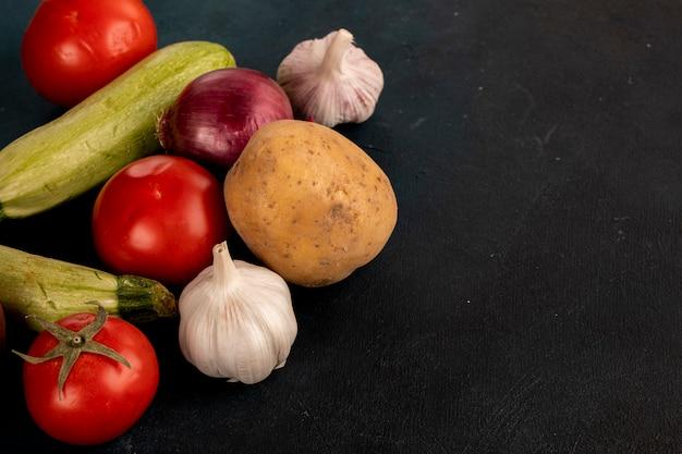 Verdure miste tra cui guanti all'aglio, patate, cipolla, zucchine e pomodori sul tavolo nero. Foto Gratuite