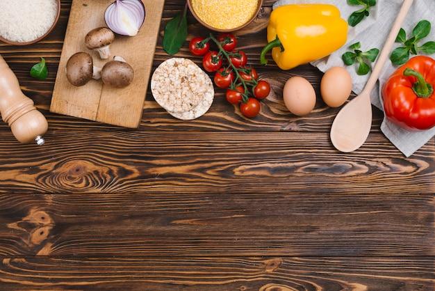 Verdure sane uova; torta di riso soffiato e polenta sullo scrittorio di legno Foto Gratuite