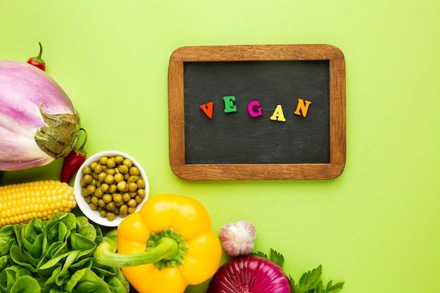 Verdure vista dall'alto su sfondo verde con scritte vegan Foto Gratuite