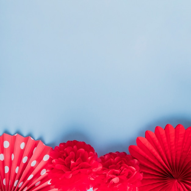 Verità di fiori di origami falsi rossi sulla superficie blu Foto Gratuite