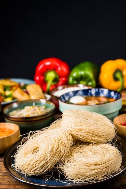 Vermicelli del riso sul piatto con alimento tradizionale tailandese contro fondo nero Foto Gratuite