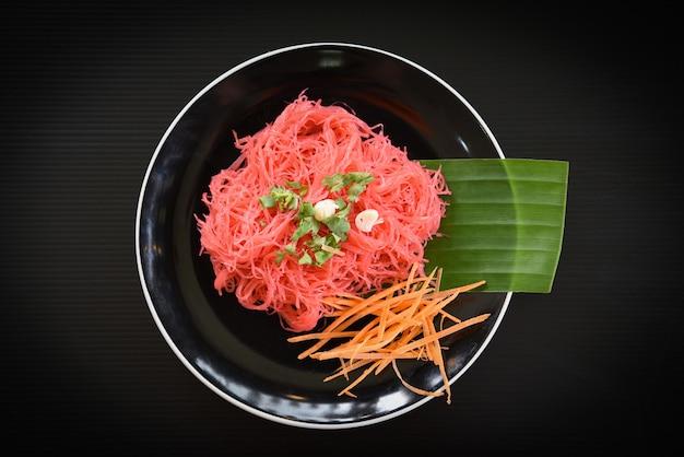 Vermicelli di riso rosa fritti e verdure mescolate le tagliatelle di riso con salsa rossa Foto Premium