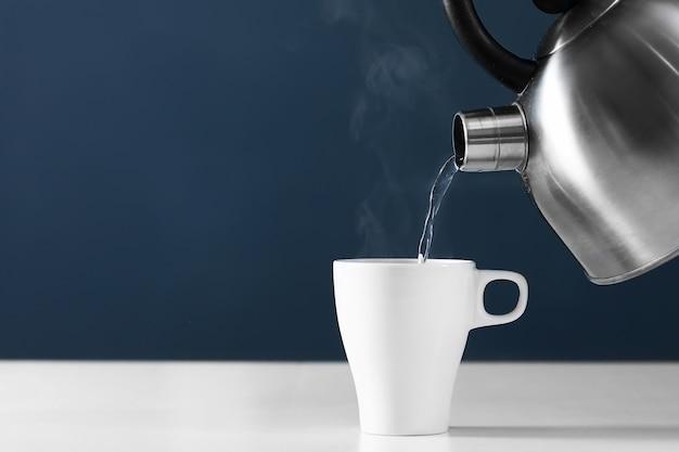 Versare acqua calda in una tazza su uno sfondo scuro Foto Premium