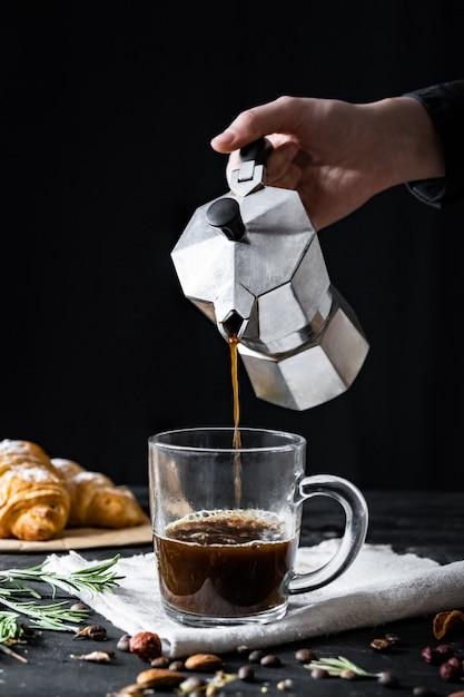 Versare il caffè da una caffettiera italiana, sparato a bassa voce. le mani maschili versano il caffè nero dal moka italiano Foto Premium