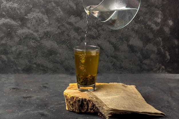 Versare il tè verde con acqua bollente da una teiera di vetro trasparente. tè antiossidante e tossinico in un bicchiere dopo la spa Foto Premium