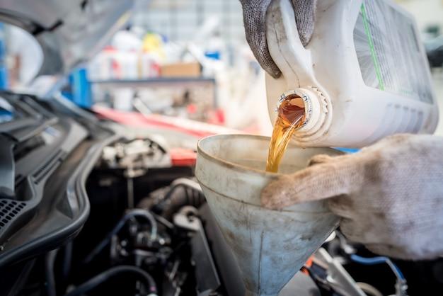 Versare olio motore nella sala macchine., olio d'oro durante il cambio dell'olio dell'automobile nell'officina riparazioni o nel centro assistenza., centro di cura interno dell'auto Foto Premium