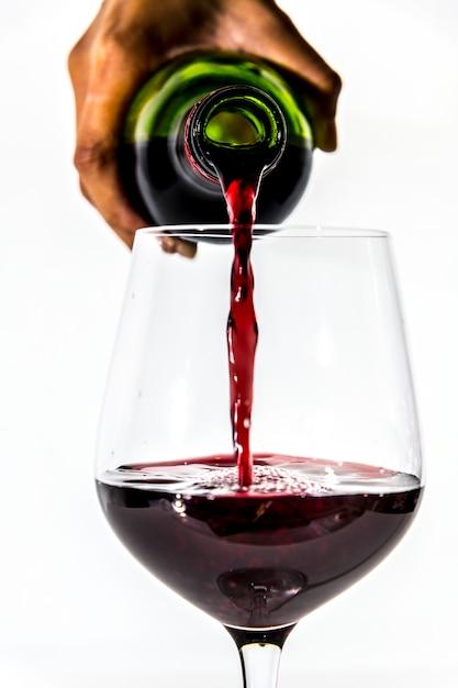 Versare un bicchiere di vino rosso Foto Gratuite