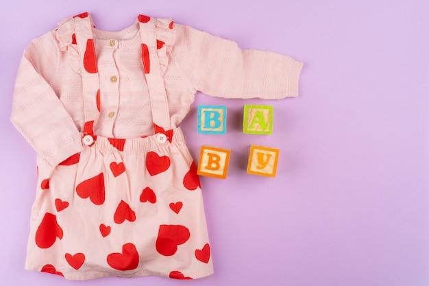 Vestiti della neonata su fondo pastello lilla Foto Premium