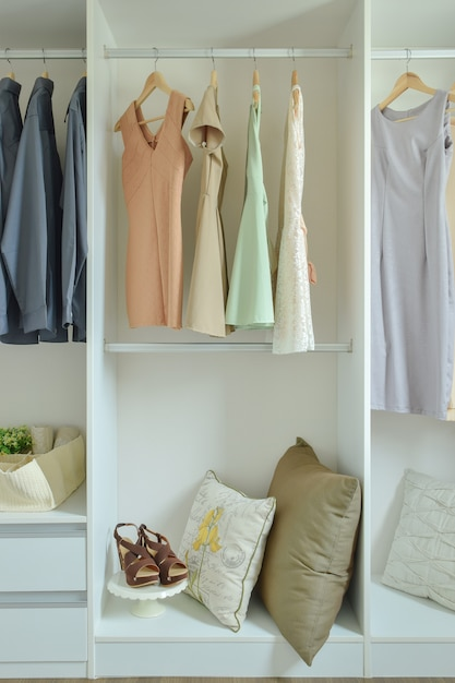 Vestiti maschii e femminili che appendono sui ganci nell'armadio Foto Premium