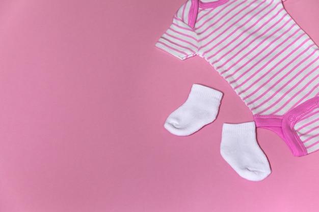 Vestiti per neonati per neonati su uno sfondo rosa con copia spazio a sinistra Foto Premium