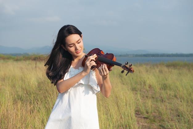 Vestito bianco dalla bella ragazza dell'asia che gioca su un violino Foto Premium