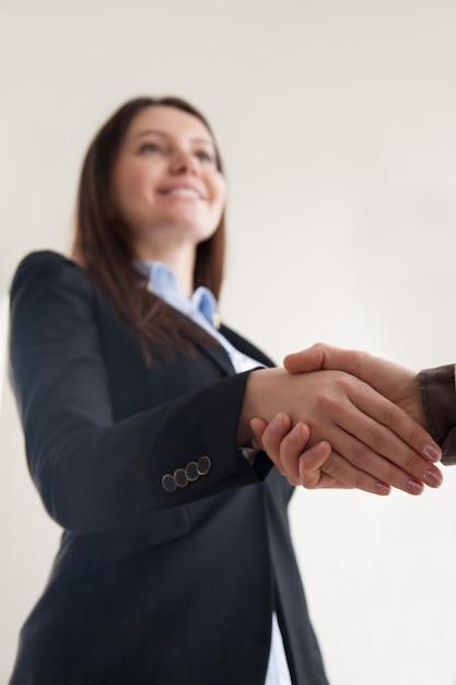 Vestito d'uso felice della donna di affari che stringe mano maschio, fuoco sulla stretta di mano Foto Gratuite