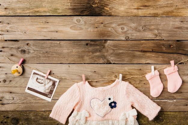 Vestito da bambino; calzini; ciuccio e foto ecografia appeso su clothesline con mollette contro la parete in legno Foto Gratuite