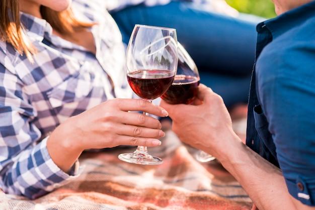 Vetri clinking dell'uomo e della donna sul picnic Foto Gratuite