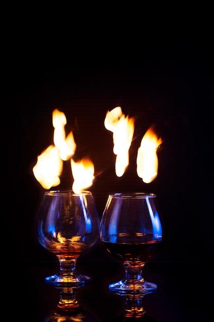 Vetri con alcool bruciante su oscurità Foto Premium