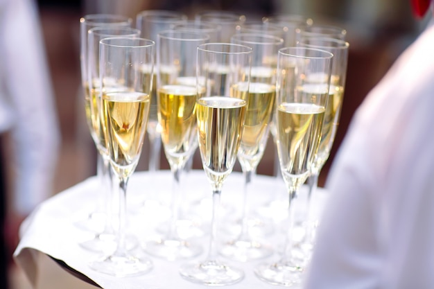 Vetri con champagne su un vassoio. incontro con gli ospiti. Foto Premium