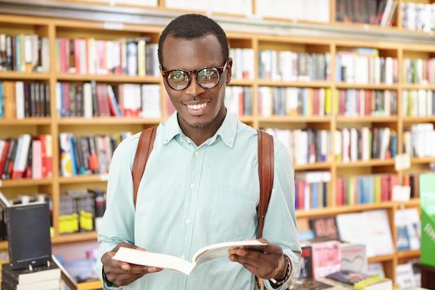 Vetri d'uso del giovane uomo di colore alla moda allegro che stanno nella biblioteca con gli scaffali di libri Foto Gratuite