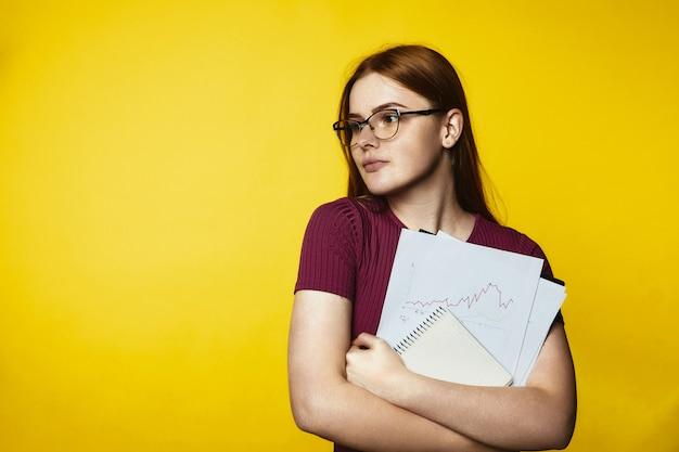 Vetri da portare della giovane ragazza della testarossa e grafici e documenti della tenuta Foto Gratuite