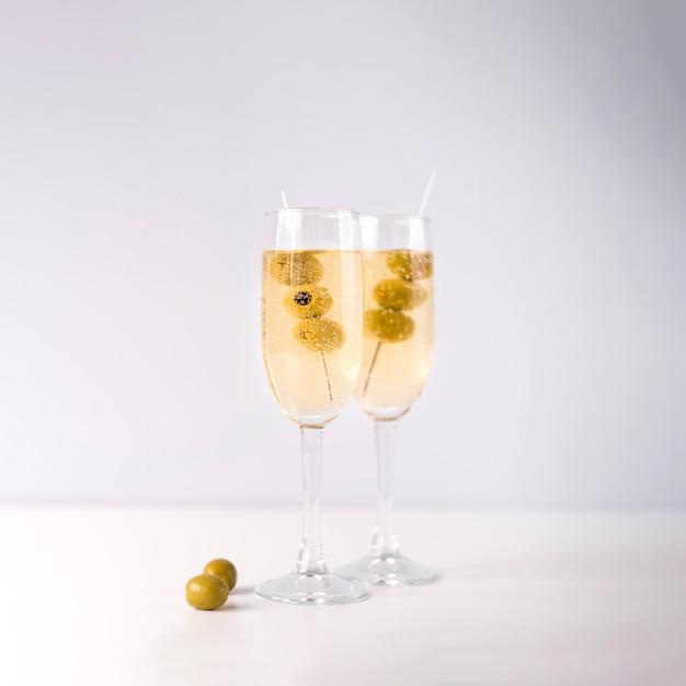 Vetri di champagne con oliva isolata su fondo bianco Foto Gratuite
