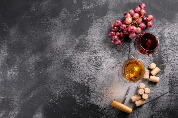 Vetri di vino di vista superiore con gli spazi della copia e dell'uva a sinistra sull'orizzontale di pietra nero Foto Gratuite