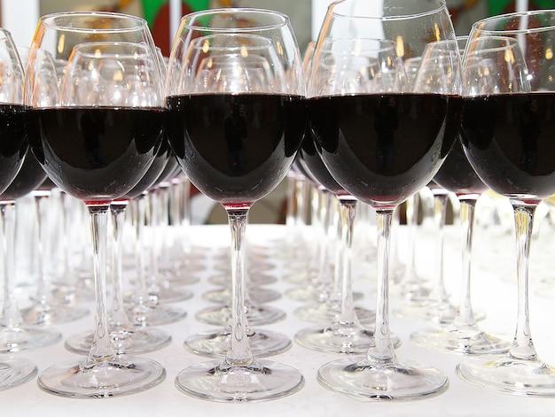 Vetri di vino rosso sul primo piano bianco della tavola Foto Premium