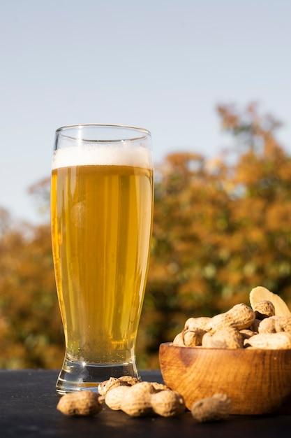 Vetro a basso angolo con birra accanto alle arachidi Foto Gratuite