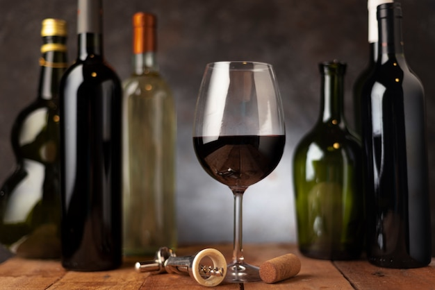 Vetro con disposizione delle bottiglie di vino dietro Foto Gratuite