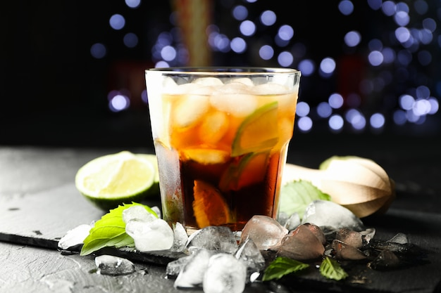 Vetro con fette di cola e lime, spremiagrumi, ghiaccio, menta su sfondo di luci sfocate Foto Premium