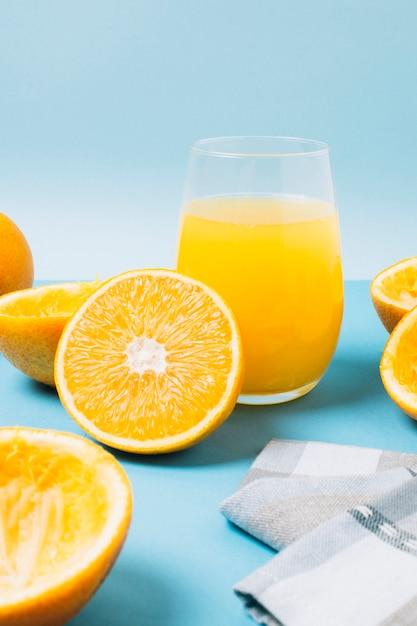 Vetro con succo d'arancia su sfondo blu Foto Gratuite