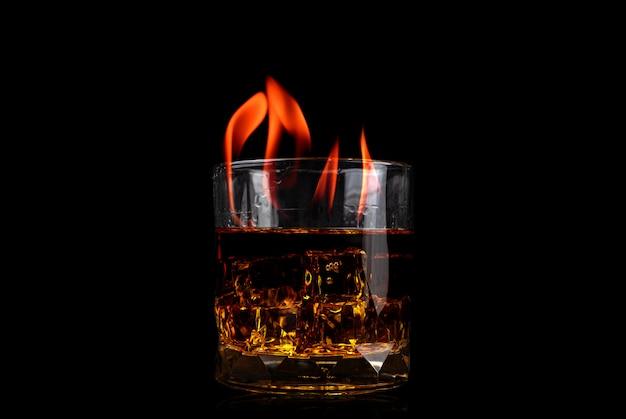 Vetro con whisky di cubetto di ghiaccio e fiamma di fuoco su sfondo nero Foto Premium