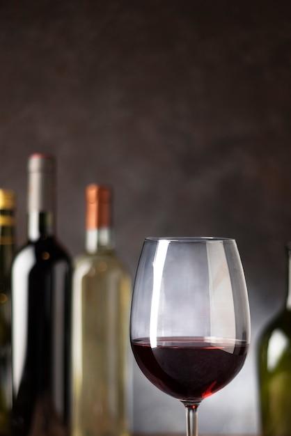 Vetro del primo piano del vino rosso con le bottiglie dietro Foto Gratuite