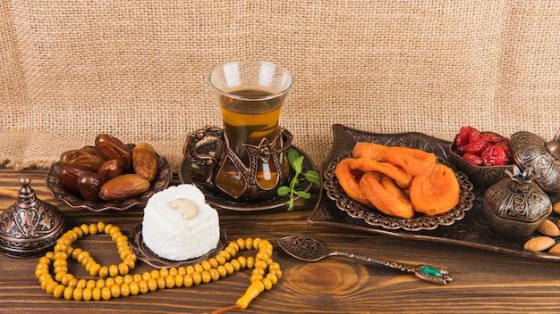 Vetro del tè con frutta secca e perline sul tavolo di legno Foto Gratuite