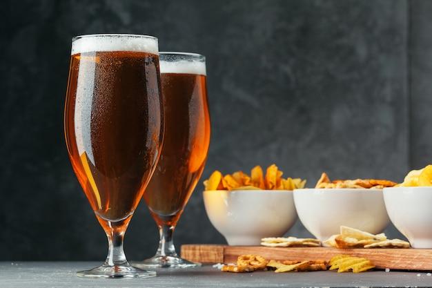 Vetro della birra chiara con le ciotole dello spuntino sulla pietra scura Foto Premium