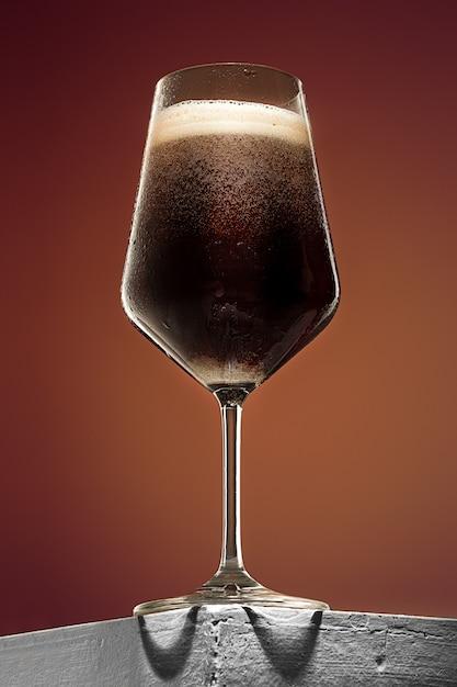 Vetro di birra scura schiumosa fredda su una vecchia tavola di legno Foto Gratuite