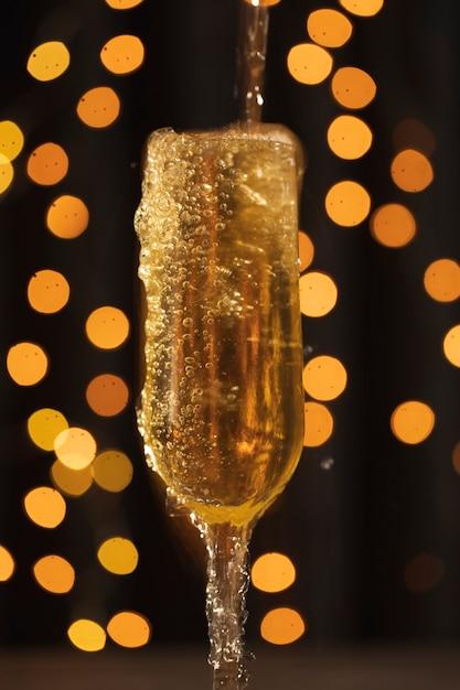 Vetro di vista frontale con champagne con schiuma Foto Gratuite