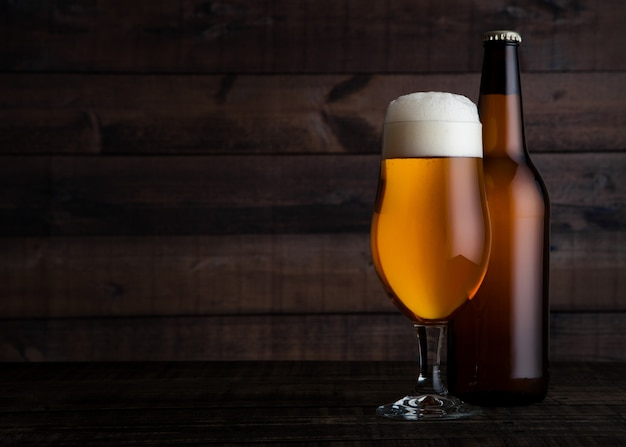 Vetro e bottiglia della birra chiara dorata con schiuma sul fondo di legno della tavola Foto Premium