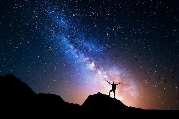 Via lattea. cielo notturno e silhouette di un uomo in piedi Foto Premium