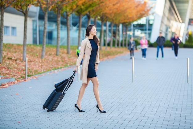 Viaggi, donna d'affari in aeroporto a parlare sullo smartphone mentre si cammina con il bagaglio a mano in aeroporto andando a gate, ragazza che utilizza il telefono cellulare per la conversazione Foto Premium