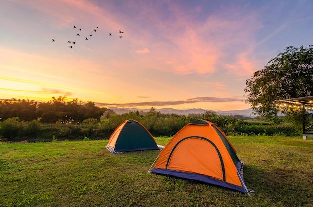 Viaggiare per diffondere la tenda in un ampio spazio aperto la sera Foto Premium