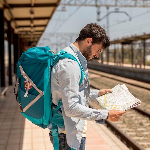 Viaggiatore con bersaglio medio guardando su una mappa Foto Gratuite