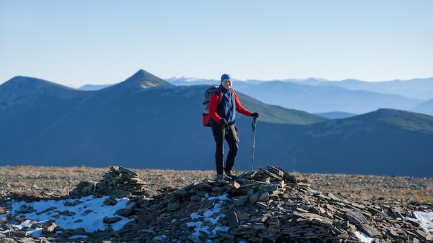 Viaggiatore con zaino e sacco a pelo atletico anziano della donna che sta sulla cima della montagna Foto Premium