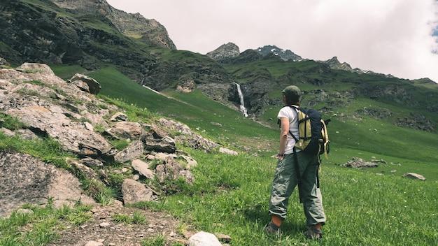 Viaggiatore con zaino e sacco a pelo della donna che fa un'escursione nel paesaggio idilliaco, nella cascata e nel prato di fioritura. Foto Premium