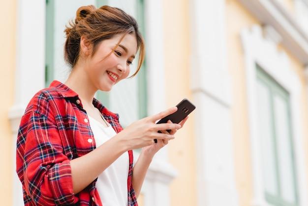 Viaggiatore con zaino e sacco a pelo turistico della donna asiatica che sorride e che usando smartphone che viaggia da solo Foto Gratuite