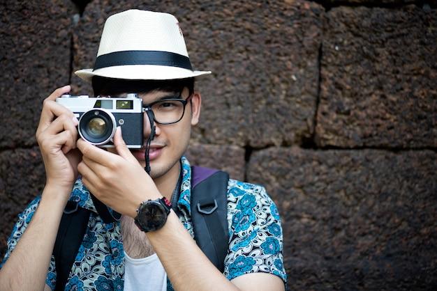 Viaggiatore del fotografo del giovane con lo zaino che cattura foto con la sua macchina fotografica Foto Premium