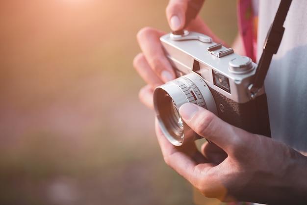 Viaggiatore del fotografo del giovane con lo zaino che prende foto con la sua retro macchina da presa Foto Premium