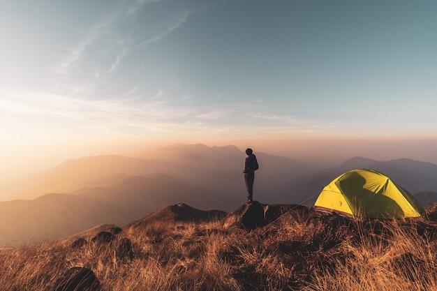 Viaggiatore del giovane che osserva paesaggio al tramonto e che si accampa sulla montagna Foto Premium
