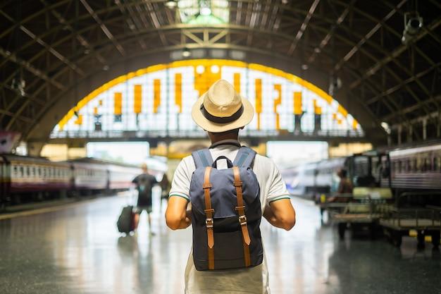 Viaggiatore del giovane con lo zaino che aspetta treno Foto Premium
