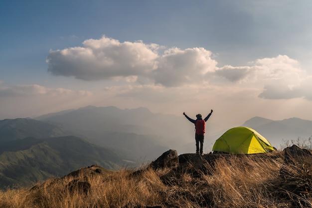 Viaggiatore del giovane con lo zaino che si accampa sulla montagna Foto Premium